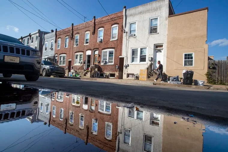 Homes on Second Street in Bridgeport that endured damage as the remnants of Hurricane Ida moved through the region are reflected in a puddle.