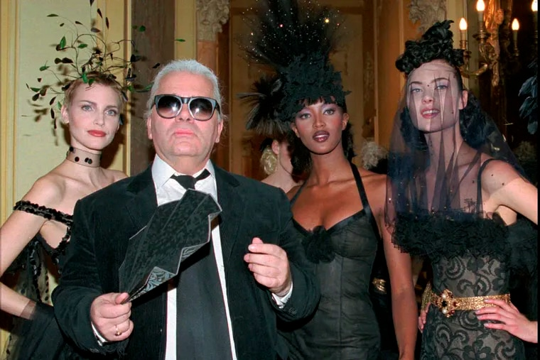 FILE - In this Tuesday January 23, 1996 file photo, German fashion designer Karl Lagerfeld, with fan, stands with German model Nadja Auermann, left, British model Naomi Campbell, second right, and an unidentified model after the presentation of Chanel's 1996 spring/summer haute couture collection, in Paris. Chanel's iconic couturier, Karl Lagerfeld, whose accomplished designs as well as trademark white ponytail, high starched collars and dark enigmatic glasses dominated high fashion for the last 50 years, has died. He was around 85 years old. (AP Photo/Lionel Cironneau, File)
