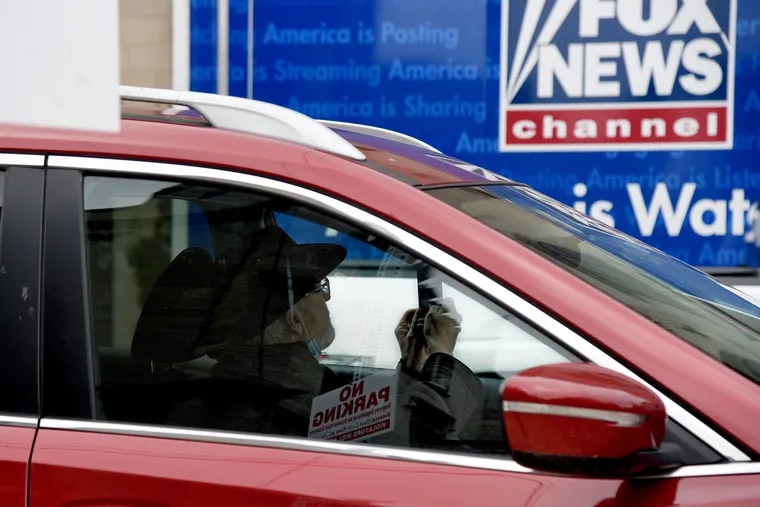 Trump supporter Jack McGovern, 67, pulls up in his car to take a picture of the Fox News tractor trailer parked outside the Scranton Cultural Center on March 4., the day before President Trump made his first visit of 2020 to the battleground state of Pennsylvania, for a Fox News town hall-style event at the former Masonic Temple and Scottish Rite Cathedral.
