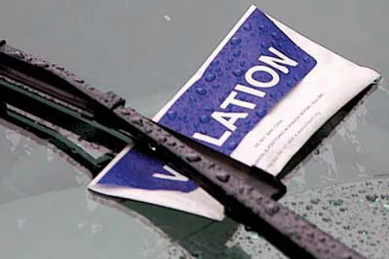 A blue and white violation and envelope left by Parking Authority Officer Ray Reichner  while patrolling on Walnut near 6th in Center City. (  John Costello / Inquirer ) Editor Note  97530 PPA28 Friday 10-25-07