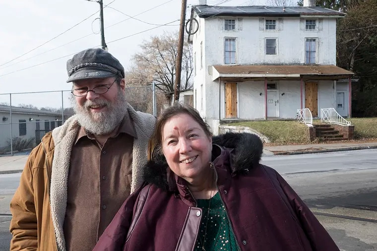 John Haigis and wife Jan pose across from a house on Main Street they are trying to save. ( ED HILLE / Staff Photographer )