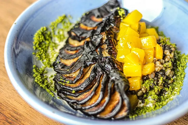 Whole eggplant cooked over the coals at Zahav is served as a vegan option over freekeh, lentils and pistachios topped with mangos pickled in amba sauce.