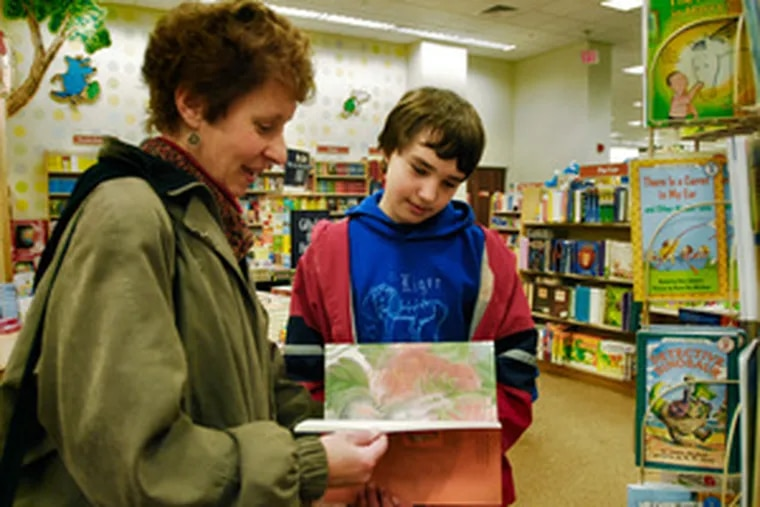 """Janet Woods and son Alex of Roxborough look at children's offerings at Barnes & Noblein Plymouth Meeting. Alex, 11, says gift cards give him the freedom to """"choose what I want."""""""