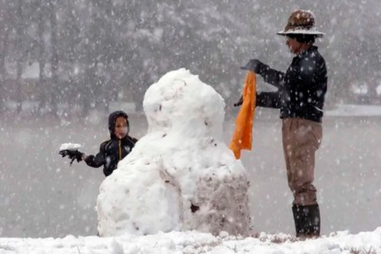 ZACHERY POWERS works on a snowman with his grandfather, Sam Adams, at Plantation Shores, Miss. yesterday, as the white stuff paid an unusual visit to the deep South.