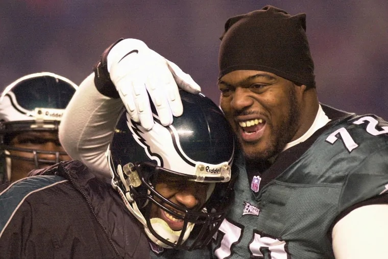 Former Eagles offensive lineman Tra Thomas (right) celebrates a touchdown with Donovan McNabb against the Tampa Bay Buccaneers during the 2000 playoffs. Thomas announced on Tuesday he had been let go by 97.5 The Fanatic, where he has co-hosted the station's morning show since October 2018.