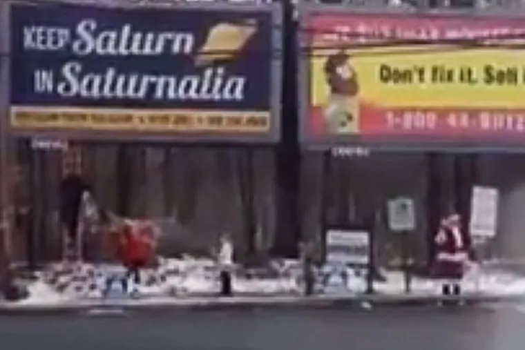 """Several protesters descended on the Pitman, N.J., billboard over the weekend. A man dressed in a full red Santa suit stood sentry in the cold for hours, holding a placard that referenced """"Obamass."""" On Sunday, a family of four attempted to shroud the sign with picture of Jesus before they were shooed away by police. (screenshot via youtube)"""