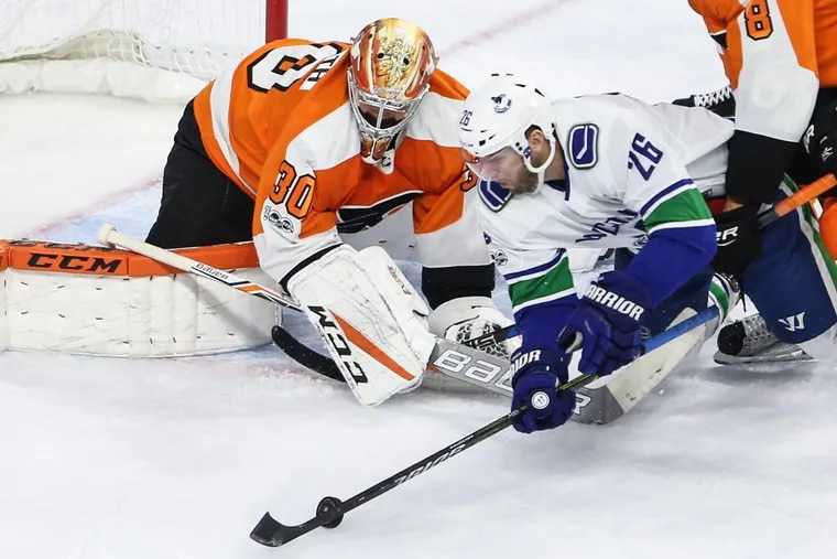 Flyers  goalie Michal Neuvirth turns away a shot by the  Canucks' Thomas Vanek  during the second period.