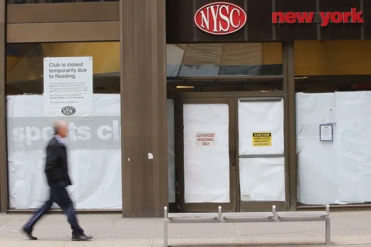A man walks past a shuttered New York Sports Club on Water Street in New York in 2013.
