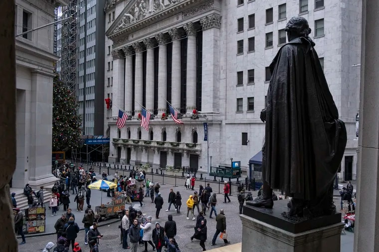 People stand near a statue of George Washington, adjacent to the New York Stock Exchange, background, Saturday, Dec. 22, 2018, at the closed Federal Hall National Memorial in New York.