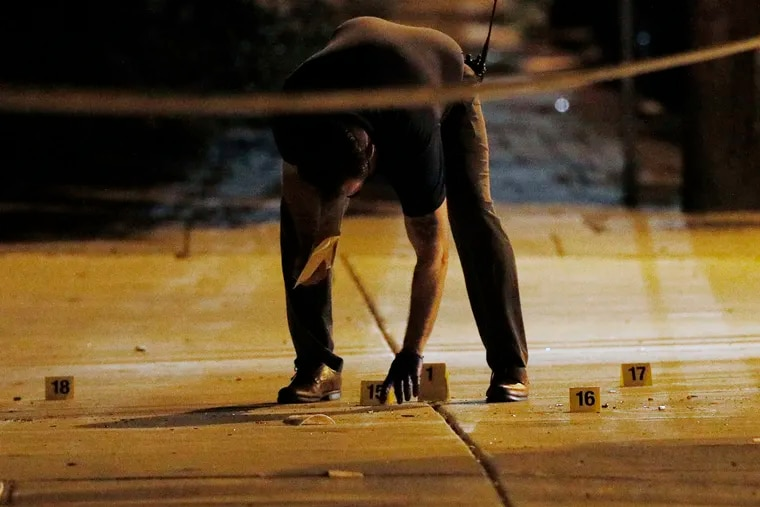 Philadelphia police investigate the scene around 38th and Poplar Street, by the Clayborn Lewis Community Center Playground. Six people were shot there just before 9:30 p.m. on Saturday night in one of the most violent weekends of the summer.