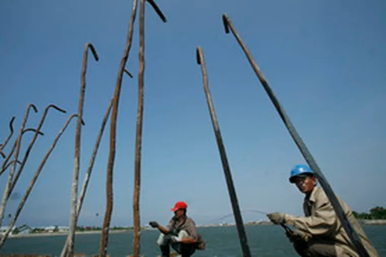 """Acehnese men work on a bridge that is to form part of a new road system in Banda Aceh, Indonesia. """"When the United Nations and the aid groups leave,"""" said the head of Aceh province's investment board, """"we have to be ready with new livelihoods."""""""