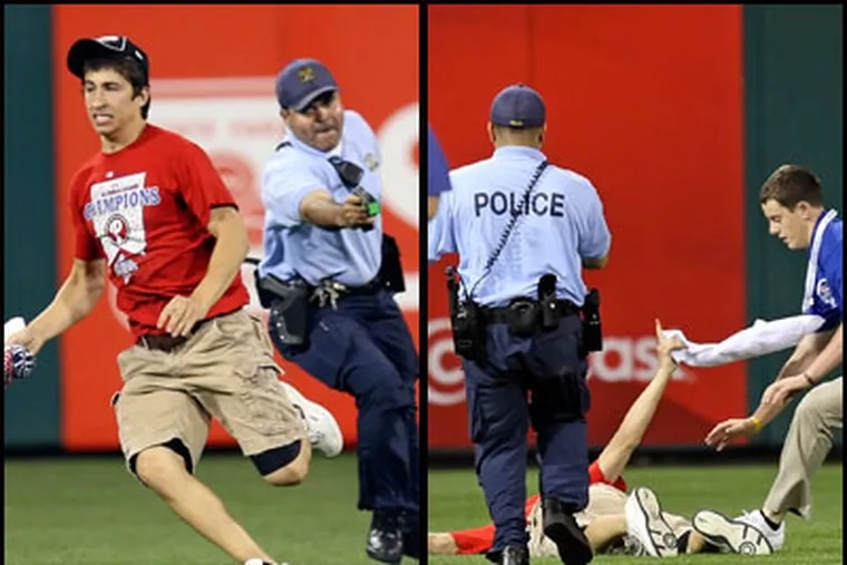 A Philadelphia police officer chases Phillies' fan Steve Consalvi, 17, who ran on the field during Monday night's game. Consalvi was felled by a taser. (Steven M. Falk / Staff Photographer)
