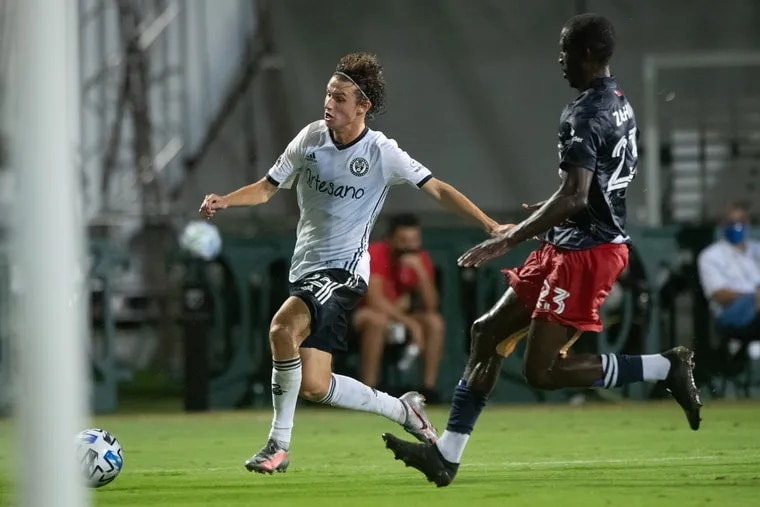 Union midfielder Brenden Aaronson, left, on the ball in front of New England Revolution midfielder Wilfried Zahibo, right, during Saturday's MLS Is Back Tournament round of 16.
