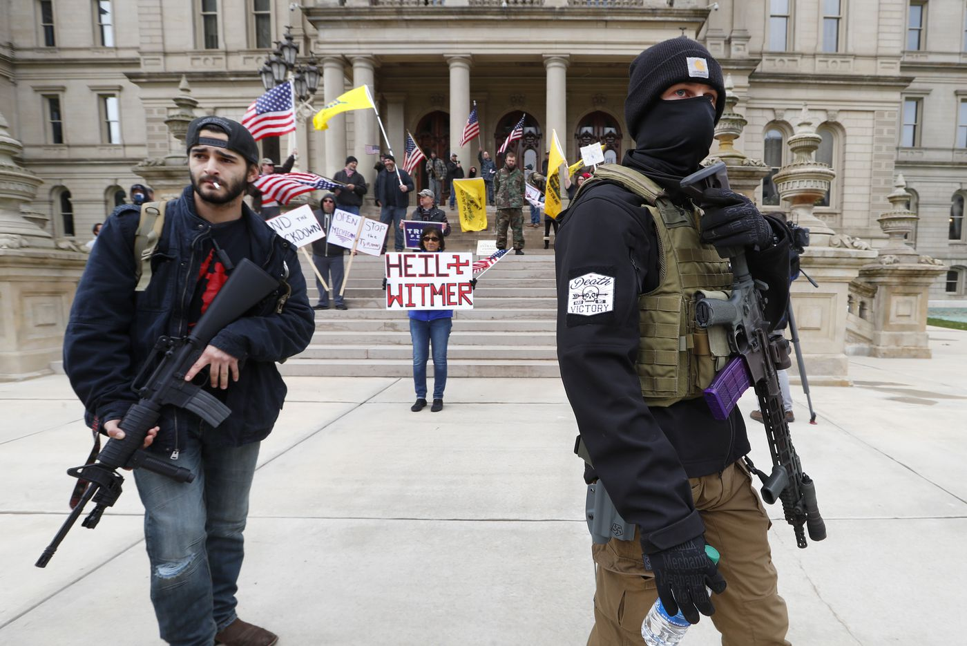 Protesters opposing business restrictions due to the coronavirus carry rifles near the steps of the Michigan State Capitol building in Lansing, Mich., on April 15, 2020.