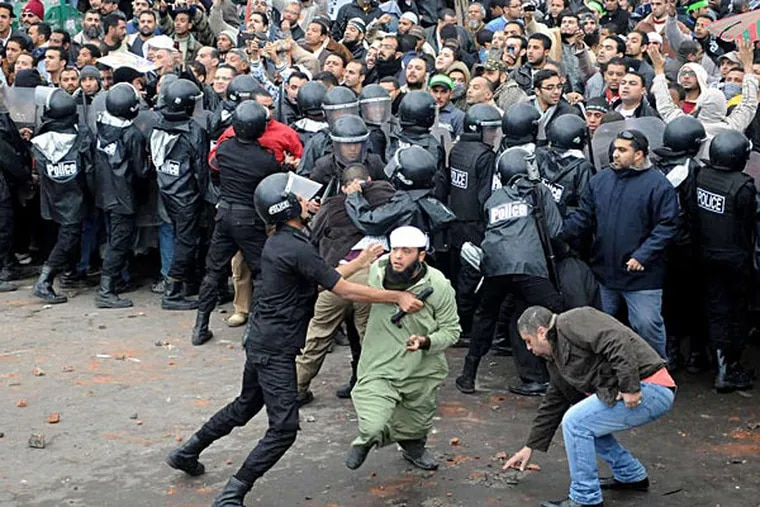 Riot police in Alexandria keep opposing crowds separate, and one officer restrains a rock-wielding protester. AP