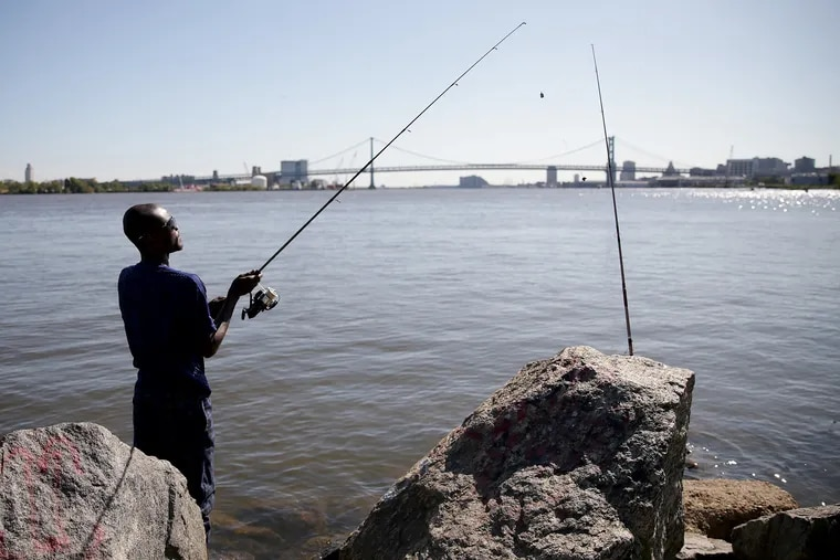 Ibrahim Fofanah, of Port Richmond, takes advantage of the nice weather as he fishes for catfish in the Delaware River from Penn Treaty Park on Sept. 17. Philadelphia is expected to get another, possibly last, taste of summer on Wednesday,