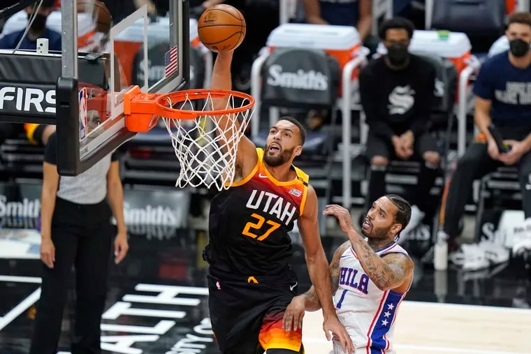 Utah Jazz center Rudy Gobert (27) dunking the ball in front of 76ers forward Mike Scott in the first half of Monday's game.