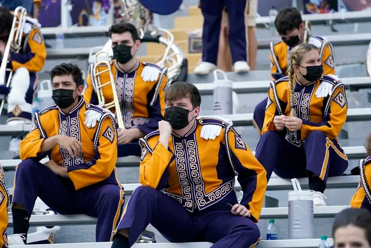 Masked members of the LSU marching band sit socially distanced from one another due to COVID-19 restrictions before a football game last year.