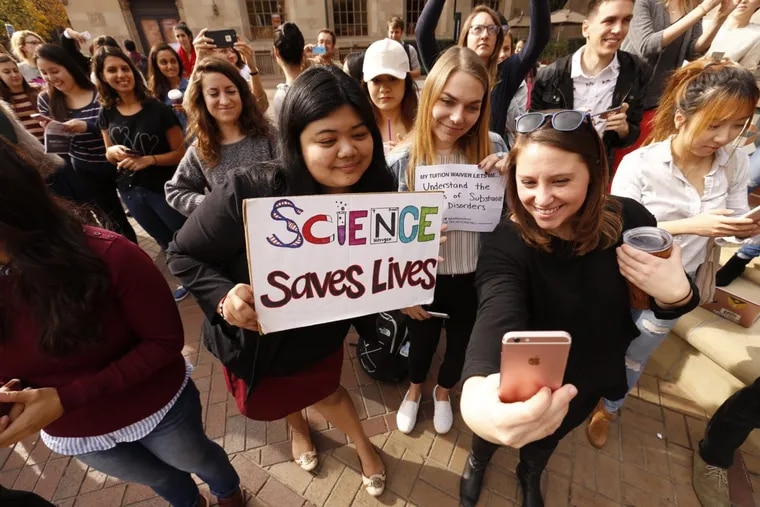 """University of Southern California graduate students Mariel Bello (from left), Nina Christie and Alyssa Morris posing for a """"selfie&quot to post online and forward to their congressman during a November rally to protest the GOP tax bill, which they say will significantly boost their taxes."""
