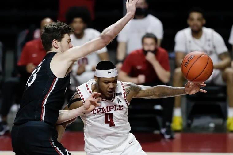 Temple forward J.P. Moorman II loses the basketball as Cincinnati center Chris Vogt defends him during the second half.
