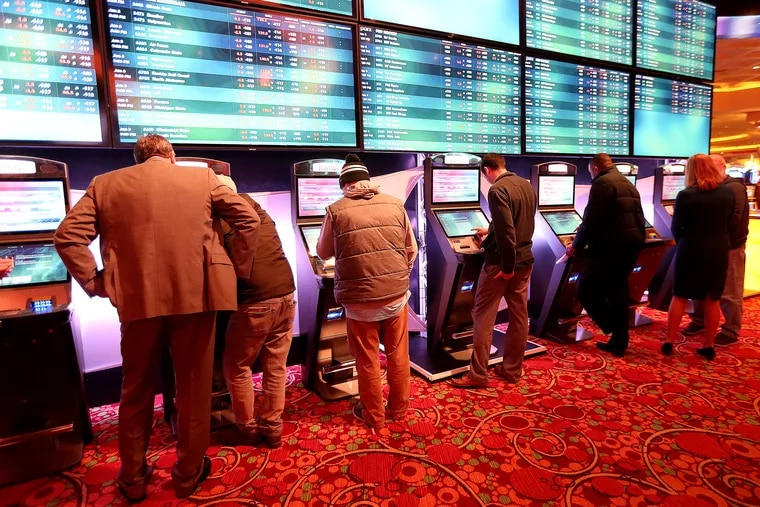 Bettors place sports wagers at some of the 26 kiosks installed throughout the Parx Casino in Bensalem, which took its first sports bets Tuesday.