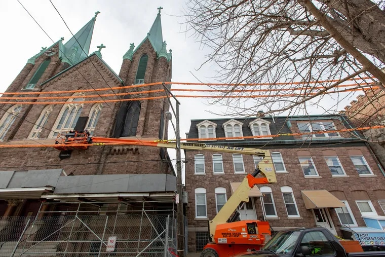 A construction crew repaired the facade of St. Laurentius in January after stones fell from the church. The physical condition of the church is now in dispute.