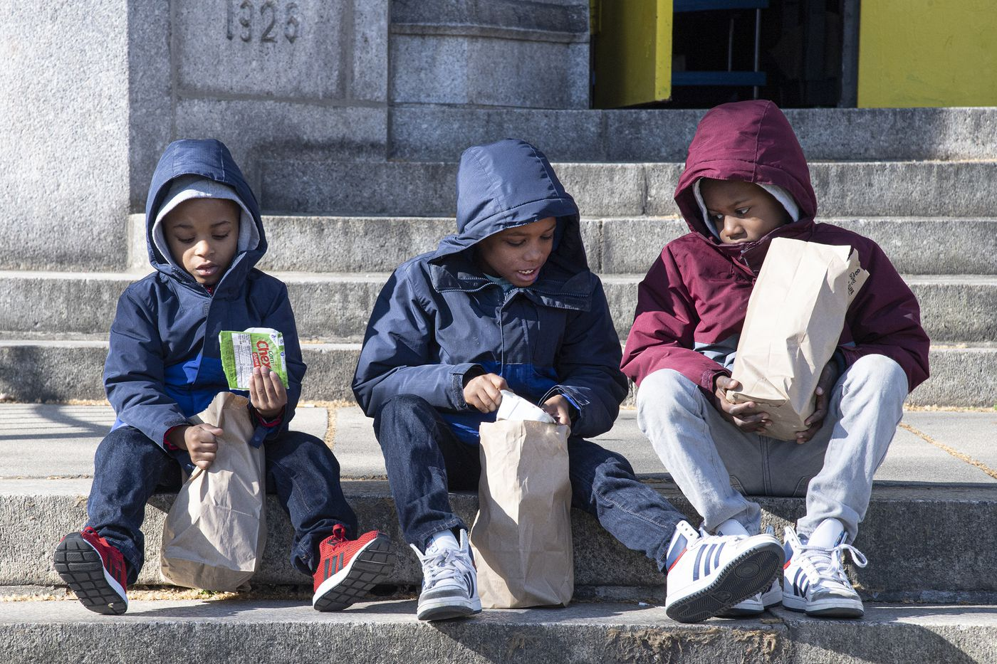 From left, Jace Butler, age-5, Mikai Warrick, age-7 and Mikel Warrick, age-7, take a close look at their meals as they seat on the steps of the Tilden Middle School where families of Philadelphia students had the opportunity to pick up packed breakfast and lunch meals during the two-week school closure. Monday, March 16, 2020.