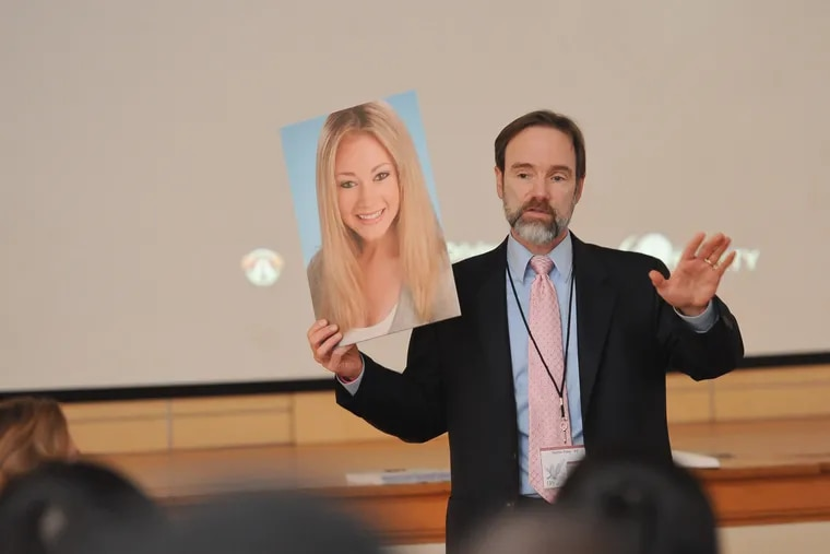 Joel Feldman speaks on distracted driving while holding a picture of his daughter Casey.