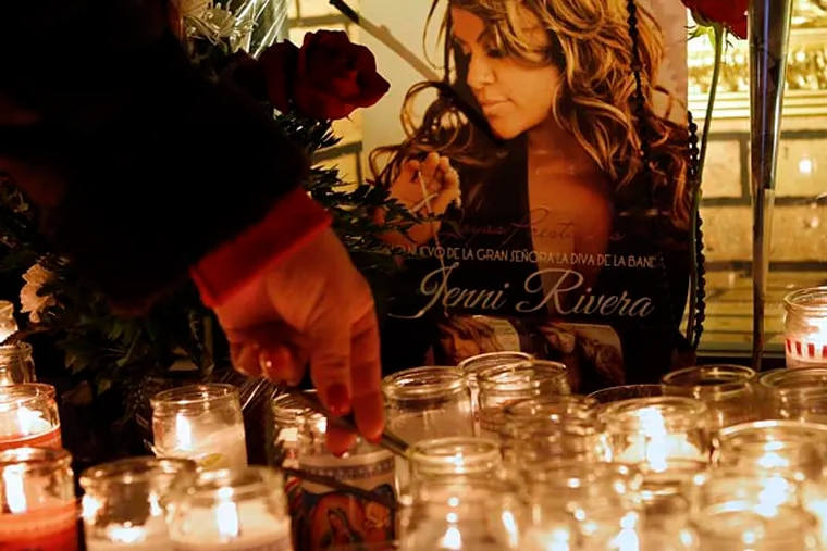 A woman adjusts a flower in front of candles and pictures displayed in tribute to singer Jenni Rivera at the Plaza Mexico shopping center in Lynwood, Calif., early Monday, Dec. 10, 2012. Authorities have not confirmed her death, but Riveraís relatives in the U.S. say they have few doubts that she was on the Learjet 25 that disintegrated on impact Sunday in rugged territory in Nuevo Leon state in northern Mexico. (AP Photo/Patrick T. Fallon)