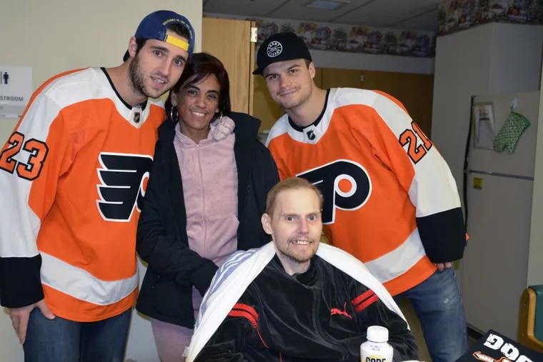 Brandon Manning (left) visiting the Temple Burn Center. A patient is next to Manning and teammate Scott Laughton, and patient Joseph Carr is in the front.