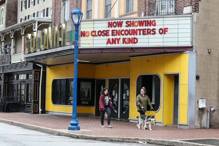 """Sydney Kook, walking """"Hutch,"""" and Niciole Troia walk under a sign of the times at The Colonial Theatre in Phoenixville on Thursday."""