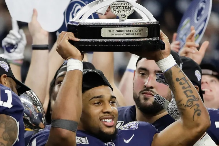 Penn State running back Journey Brown raises the Cotton Bowl's most outstanding offensive player trophy after winning the award in the Nittany Lions' victory over Memphis.