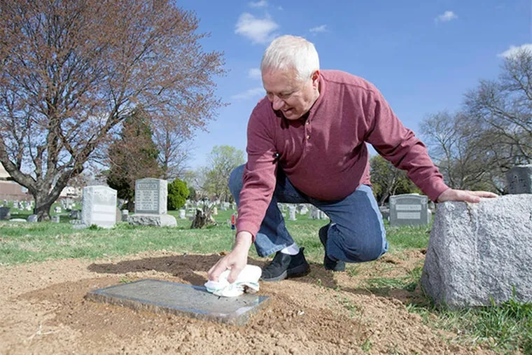 John DeVos cleans off his brother Michel's recently reset burial stone at Greenmount Cemetery.