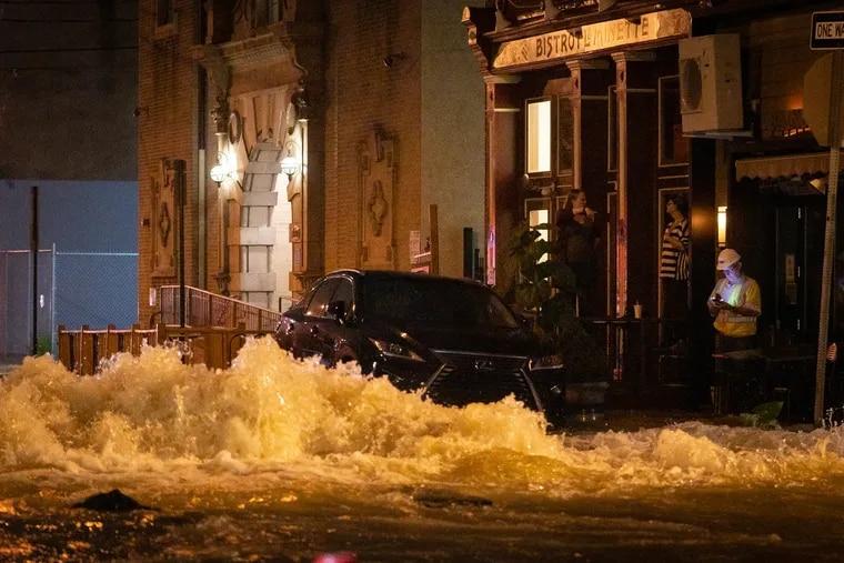 Water gushes from a broken 30-inch main on 6th Street near Bainbridge Street early Sunday.