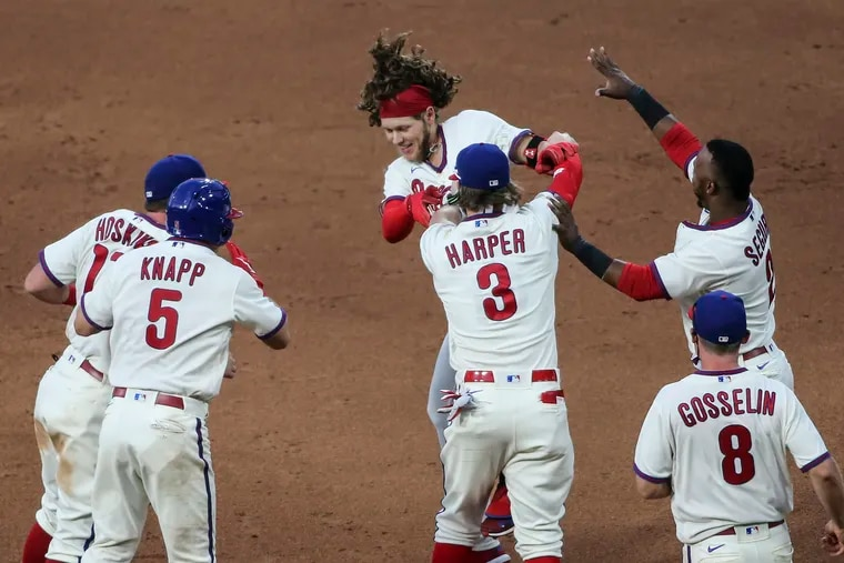 Alec Bohm is surrounded by his teammates after delivering a game-winning hit against the Boston Red Sox last season.