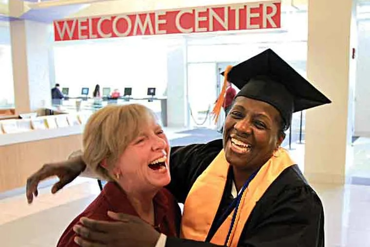 Forty years after dropping out of high school to have a baby, Jackie Hill, 55, will graduate from Montgomery County Community College this week, the first of her nine siblings to earn a degree. She says thank you to her financial aid couselor Denise Nuccio, before graduating ceremonies begin May 23, 2013. ( DAVID SWANSON / Staff Photographer )