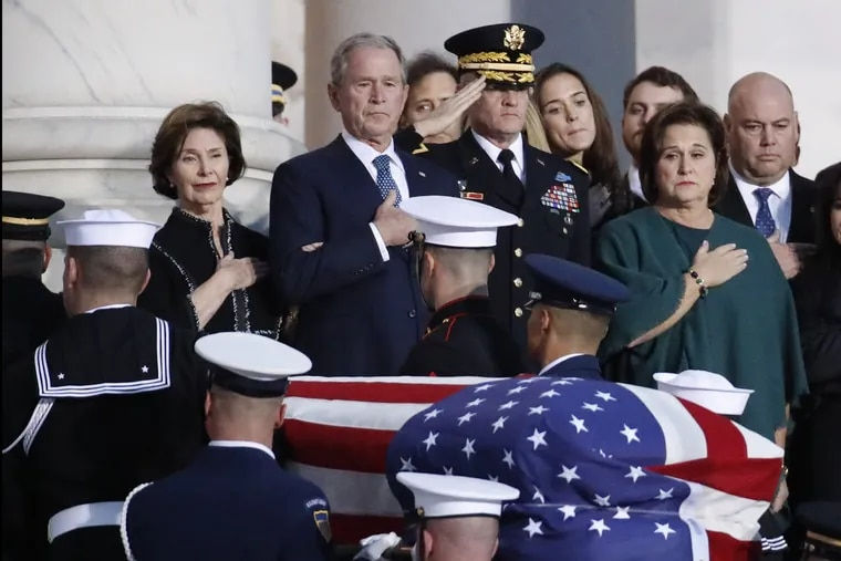 Former President George W. Bush, Laura Bush, left, and other family members watch as the flag-draped casket of former President George H.W. Bush is carried by a joint services military honor guard to lie in state in the rotunda of the U.S. Capitol.