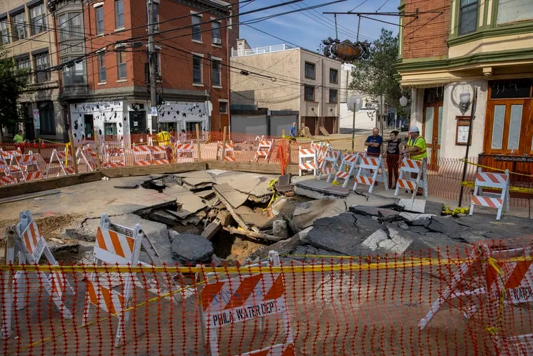 Philadelphia Water Department barricades surround the site of a water main break at the intersection of Bainbridge and South 6th Streets last month. Paying for such repairs has helped fuel rate increases.