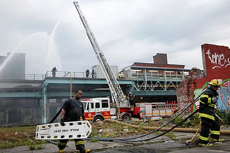 Philadelphia firefighters battled a multi-alarm warehouse blaze along North Front Street, just below Girard Avenue in the Fishtown section of the city, early Tuesday. This picture shows them gathering up their equipment. (Alejandro A. Alvarez / Staff Photographer)