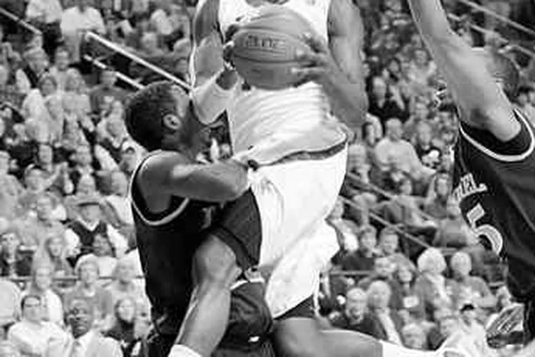 Drexel's Jamie Harris (left) fouls Kentucky's John Wall as the Wildcat drives to the basket. Wall, a freshman superstar, scored 16 points as the third-ranked Wildcats cruised to a 88-44 victory.