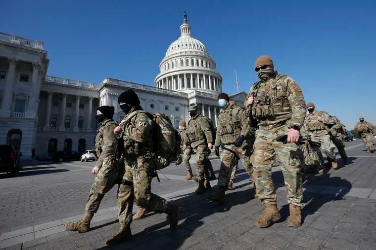 Members of the National Guard arrive on Capitol Hill during the impeachment debate and vote on Wednesday.