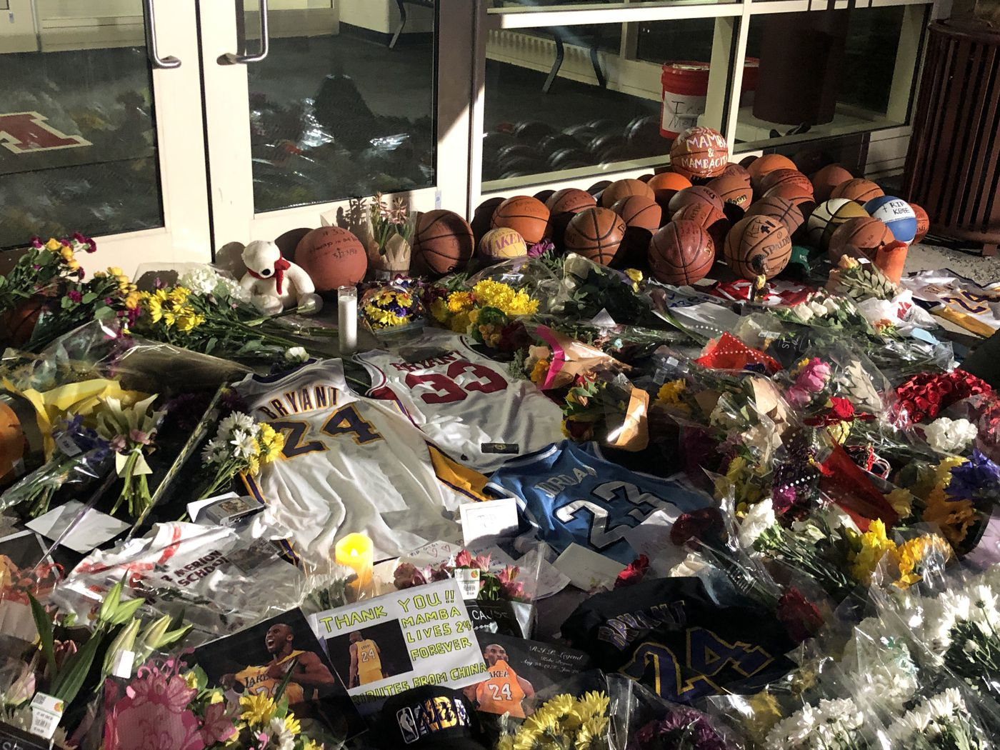 Basketball jerseys lay on the ground amid a pile of items at a makeshift memorial to Kobe Bryant outside the Bryant Gymnasium at Lower Merion High School. Among them: A Kobe Bryant No. 33 Lower Merion High School Jersey. He couldn't wear No. 33 when he played for the Lakers — the number had been retired in honor of Kareem Abdul-Jabbar.