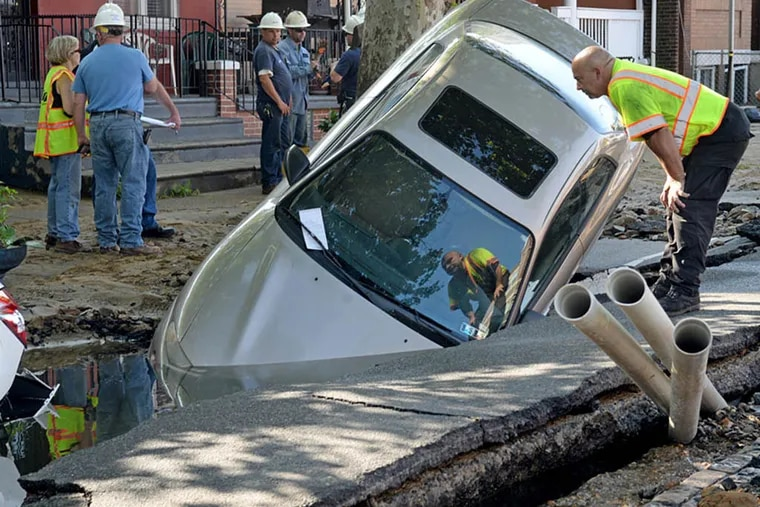 A 130-year-old water main ruptured early yesterday on 52nd Street near Wyalusing Avenue, damaging homes and sucking cars into crumbling sinkholes. The main dated back to 1885, and city officials were working last night to find out why it burst. TOM GRALISH / STAFF PHOTOGRAPHER