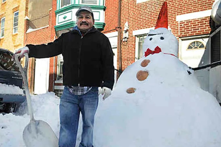 German Guerrero, with the 6-foot snoman he made in South Philly. (Sarah J. Glover / Staff)