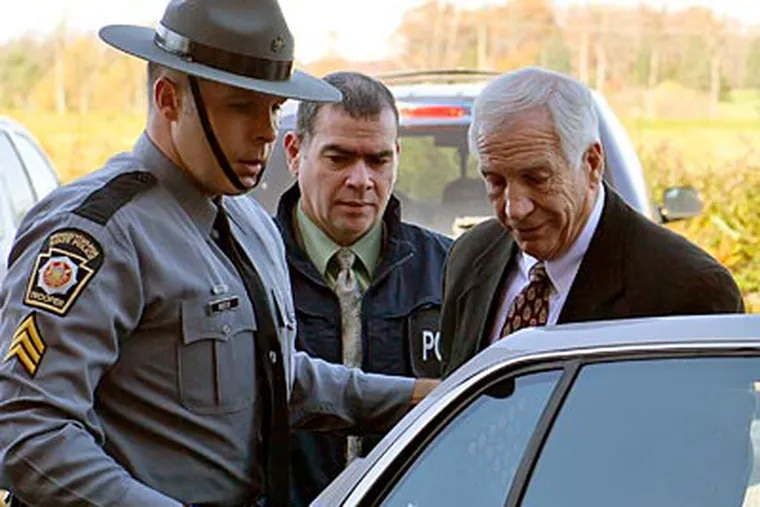 Former Penn State coach Jerry Sandusky is put in the back of a police car. (Andy Colwell/The Patriot-News/AP)