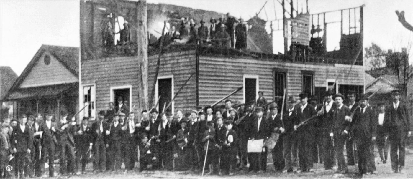 Armed members of a white supremacist mob pose together after burning down the offices of the Daily Record, a Black newspaper in Wilmington, N.C., in November 1898 during what is now known as the Wilmington Massacre.