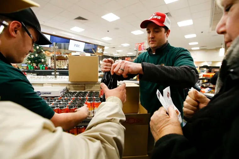 Wawa employee Matthew Parris hands out bottles of the Wawa and 2SP Brewery Company new Winter Reserve Coffee Stout beer to customers at the Wawa in Chadds Ford, PA on Friday, December 6, 2019.  Parris manages another Wawa store and is helping with the release of the beer.  Beer fans waited in line for the Winter Reserve Coffee Stout Beer from Wawa and 2SP Brewing Company.