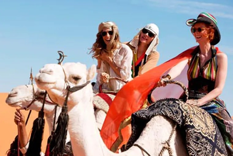 """Sarah Jessica Parker, Kim Cattrall and Cynthia Nixon climb aboard camels in """"Sex and the City 2."""" (Warner Bros. Pictures)"""