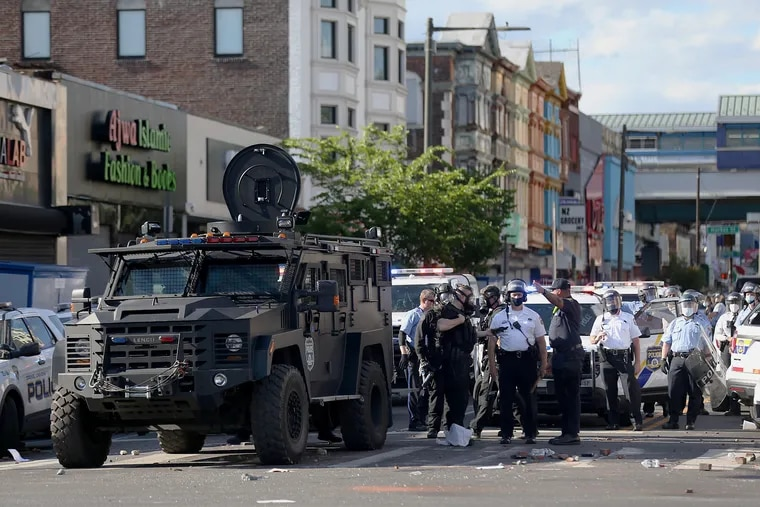 Philadelphia Police Department officers gather after SWAT members fired tear gas from an armored truck in an apparent effort to clear a crowd of people breaking into the Foot Locker at 52nd and Chestnut Streets in West Philadelphia on Sunday, May 31, 2020. The Philadelphia Police Foundation's donations last year included money for SWAT equipment.