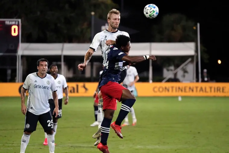 Union forward Kacper Przybylko going up for a header against New England Revolution forward DeJuan Jones (front) during the MLS tournament's round of 16.
